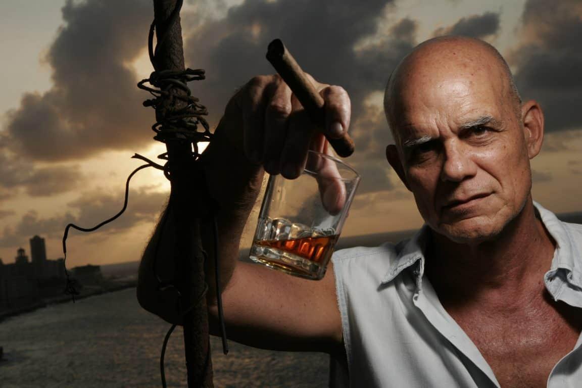Pedro Juan Gutierrez, kubanischer Schriftsteller und Author der Schmutzige Trilogie von Havanna, mit Rum Glas (Havana Club Anejo) und kubanischer Zigarre (Montecristo), auf dem Dach seiner Wohnung in Centro Habana, den Malecon überblickend. // Cuban writer Pedro Juan Gutierrez